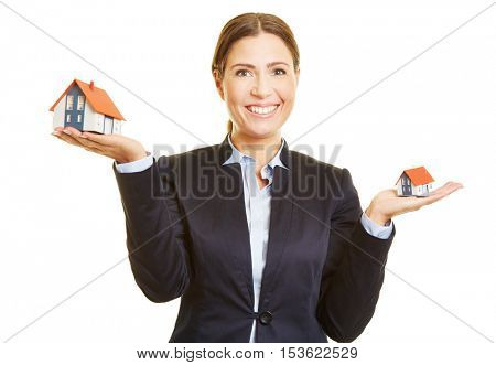Smiling real estate broker holding two small houses on her hand