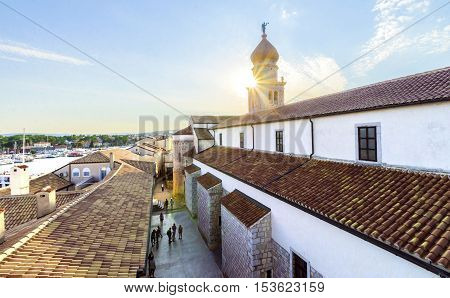 Krk town Croatia island at sunset. Sun burst through the bell tower of the Church of the Assumption of Blessed Virgin Mary with an angel holding a trumpet the port and ceramic tiles on the roof houses.