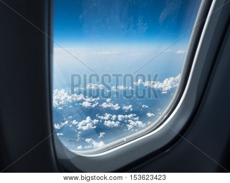 View of the cloudy sky from the airplane's window. Picture of the blue sky with white clouds. The foto that was made above the white cumulus.