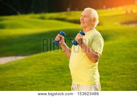 Old man holding dumbbells. Person on nature background. Training program for retired athletes. Don't lose self esteem.