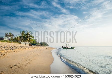 Beautiful blue sea wave and fishing boat on white sand beach for vacations in Hua Hin, Prachuap Khiri Khan Province, Thailand.