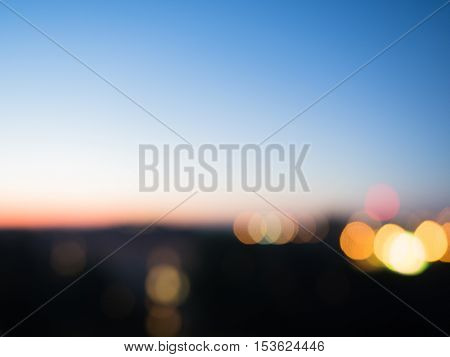 Picture of the evening City. The blurred picture of the blue sky with out of Focus City Lights. Blurred background of the evening City. Beautiful sunset with out of focus lights.
