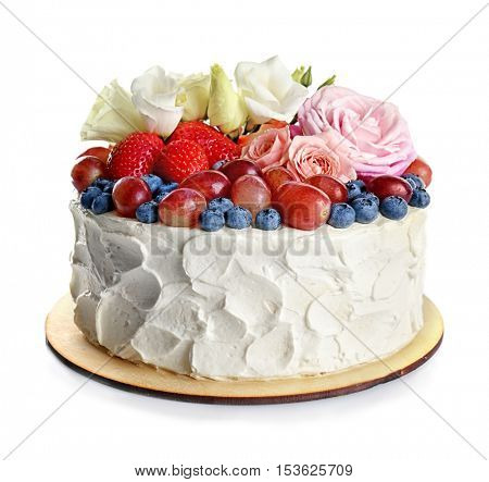 Delicious cake decorated with berries and flowers on white background