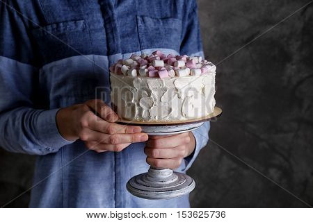 Woman holding delicious cake with marshmallows