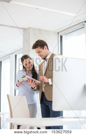 Young businessman with female colleague using digital tablet in office