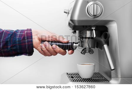 Professional espresso machine pouring strong looking fresh coffee into a neat ceramic cup