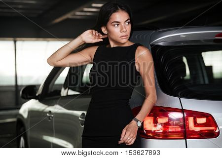 Pretty young business woman in black dress standing near her car on parking