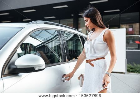 Beautiful young woman standing and opening the door in her car outdoors