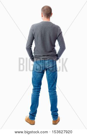 Back view of man in jeans. Standing young guy. Rear view people collection.  backside view of person.  Isolated over white background.  guy in a gray sweater standing with folded hands in his pockets.