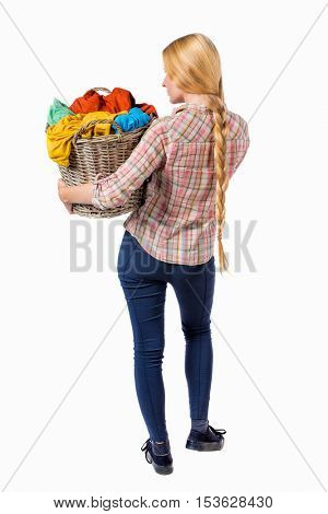 Back view of woman with  basket of dirty laundry. girl is engaged in washing. Rear view people collection.  Girl with braided hair in a braid holding a basket with colorful linens.