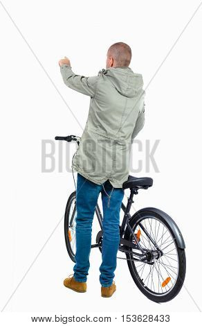 back view of pointing man with a bicycle. Cyclist in parka jacket keeps the wheel of a bicycle. Rear view people collection.  backside view of person. Isolated over white background.