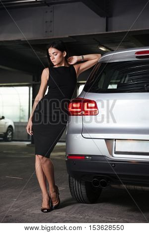 Full length portrait of beautiful young woman in black dress standing and posing near her car