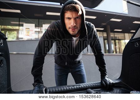 Criminal young man in black hoodie and gloves standing and looking at car trunk