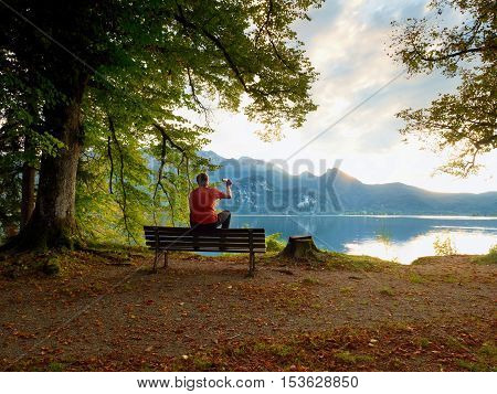 Man Sit On Wooden Bench At Mountain Lake . Bank Under Beeches Tree