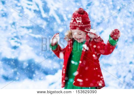 Little girl in red jacket and green knitted dress catching snowflakes in winter park on Christmas eve. Kids play outdoor in snowy winter forest. Children catch snow flakes on Xmas. Toddler kid playing.