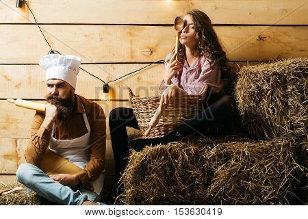 Pensive man chef cook or baker with beard and moustache in hat toque and cute girl cookee teenager in apron sit on straw bales on rustic background