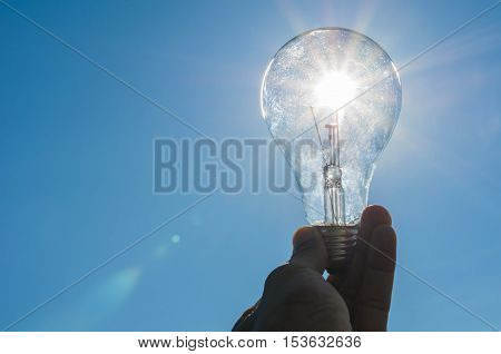 hand hold a light bulb with sunshine power concept white blue sky background