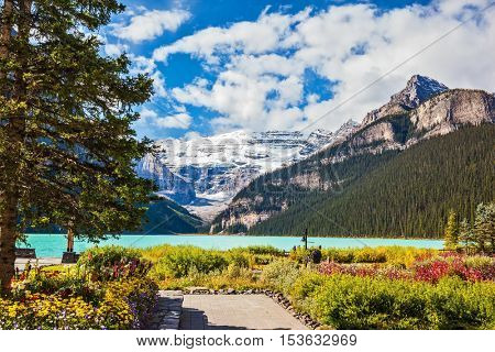 Banff National Park, Rocky Mountains, Canada. The picturesque promenade at Lake Louise. The emerald waters of the lake surrounded by mountains, glaciers and pine forests