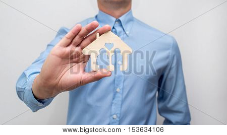 man holding in his hand a symbol of home and family