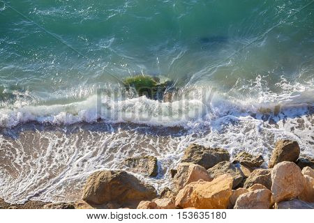 Large coastal rocks and soft waves. Nature on sunny day