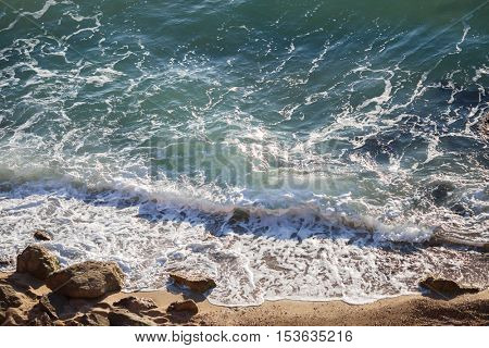 Beautiful sea landscape with crystal clear waves and coastal boulders