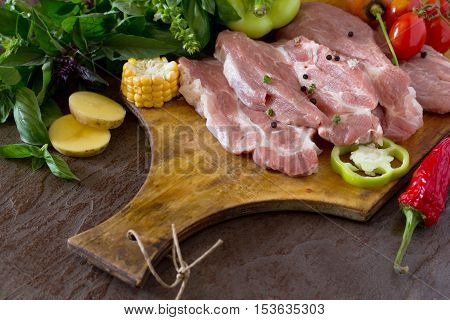 Fresh Raw Meat Pork Fillet With Vegetables On A Concrete Background. Copy Space.