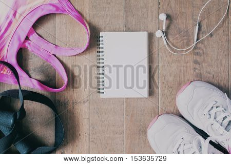 Flat lay of empty notebook pink color sport bra sport equipment earphone and sneaker on wood background. Sport fashion Sport accessories top view copyspace with film color filter