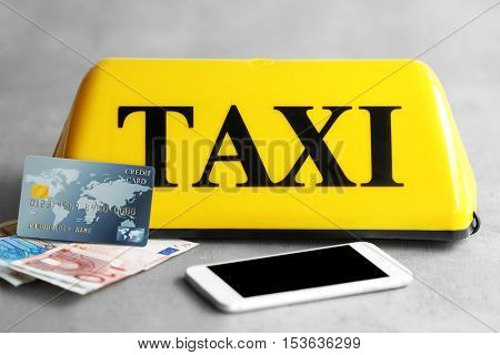 Yellow taxi roof sign with phone, credit card and Euro banknotes on gray background, closeup