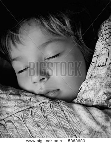 Cute boy sleeping in his bed, in black and white tones
