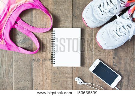 Flat lay of empty notebook pink color sport bra cellphone and sneaker on wood background. Sport fashion Sport accessories top view copyspace