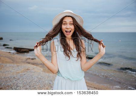 Cheerful funny girl in hat having fun on the beach