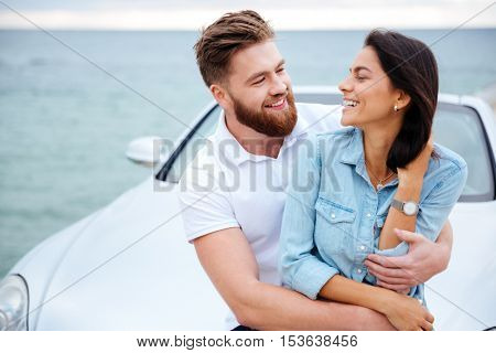 Young beautiful couple embracing while standing near car at the seaside