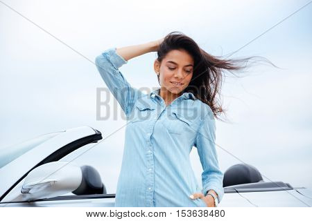Attractive young woman standing near her new car outdoors