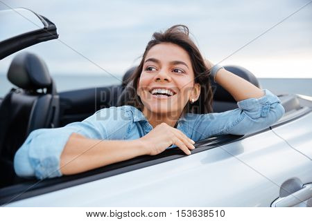 Smiling brunette woman resting in her cabriolet parked on the beach