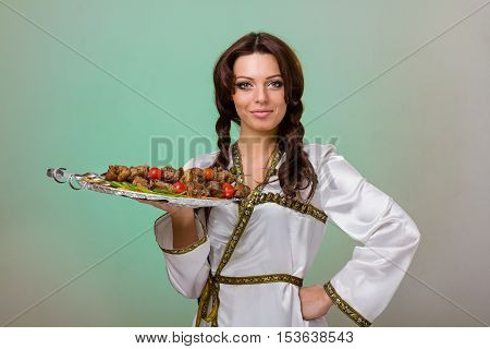 Woman hold plate with meat decorated with fruits and vegetables for dinner evening on green background