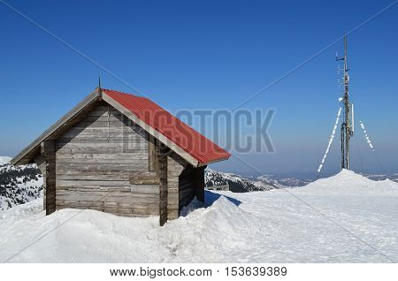 The end of winter wooden shelter and antenna on the top of the mountin sunny day and melting snow