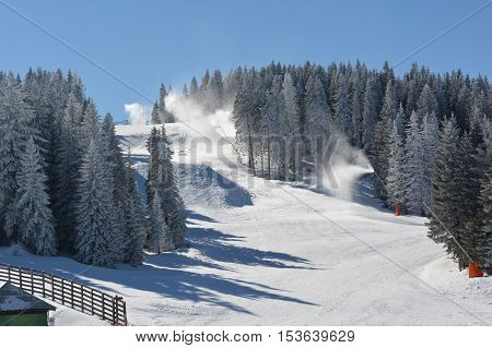 The end of ski day several snow guns in action overlapping of ski slopes with artificial snow