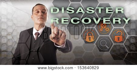 Experienced corporate manager pressing DISASTER RECOVERY on an interactive screen. Information technology concept for resuming normal business activities after disruption of business continuity.