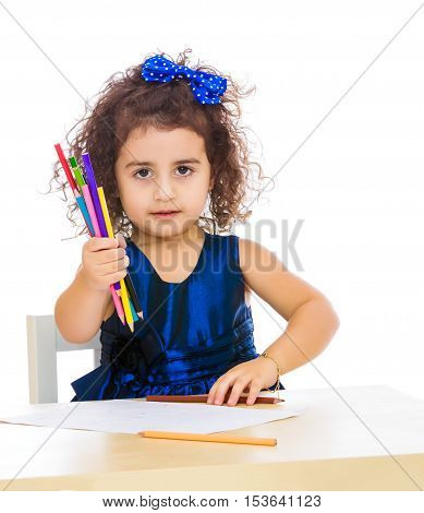 Cute little girl in blue dress, holds a lot of pencils . She paints at a table in a Montessori kindergarten.Isolated on white background.