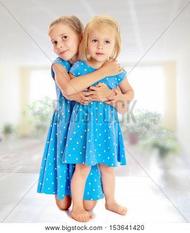 Two charming little girls, sisters , in identical blue dresses with polka dots , cuddling.On the background of the school hall with large Windows.