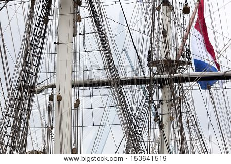 Rigging of a historical sailing ship with a dutch flag and the Rotterdam Erasmus bridge in the background