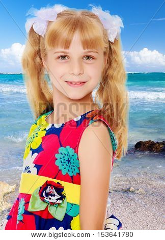Sweet, adorable little girl with long blonde ponytails on her head tied with white bows. Close-up.On the background of sea beach, warm sea and blue sky with clouds.