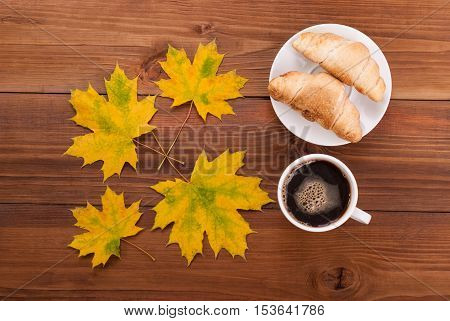 Coffee croissants and maple leaves on wooden background.