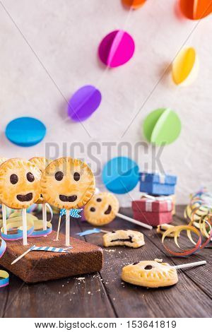Homemade shortbread smiley cookies with dark chocolate on stick called pie pops. Children's party background.