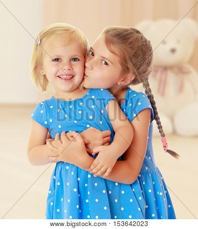 Two charming little girls, sisters , in identical blue dresses with polka dots. Older sister kissing the younger on the cheek.In the background children's room where the sitting Teddy bear.