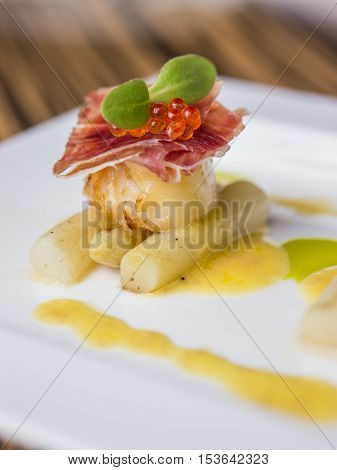 Seared scallops with salmon roe ham and asparagus on plate
