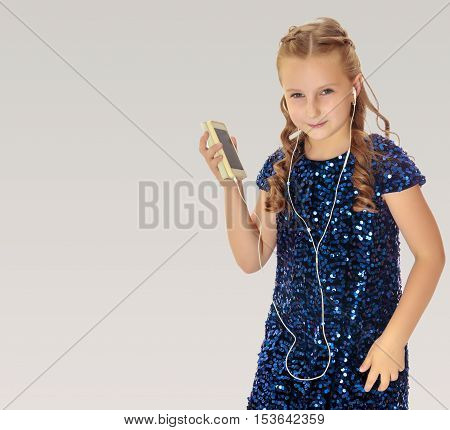 Elegant little girl in a festive, glittering, blue dress, holding a mobile phone . She listens to music through headphones.On a gray background.