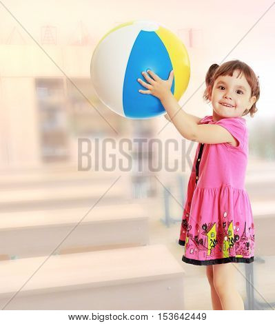 Happy little girl with pigtails on the head , in a pink dress. The girl lifted a large, inflatable striped ball.On blurred background of a school class where there are desks and cabinets.