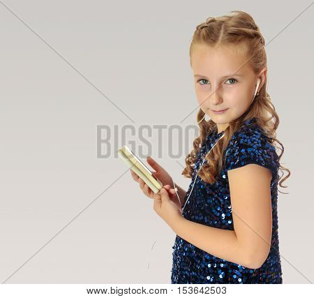 Caucasian little girl in a festive, glittering, blue dress, holding a mobile phone . She listens to music through headphones.On a gray background.