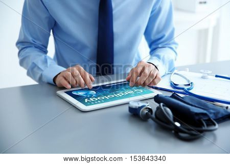 Cardiologist working with tablet at office. Health care concept.